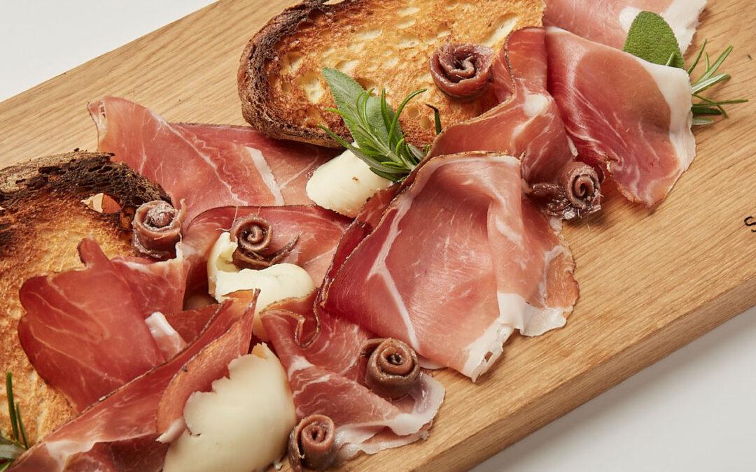 Pain grillé avec speck, anchois en boucles et beurre