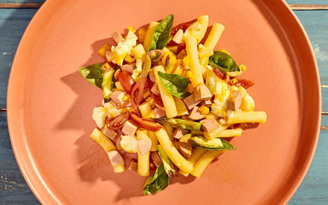 Cold pasta with pork and turkey Wurstel, eggs, basil and marinated vegetables