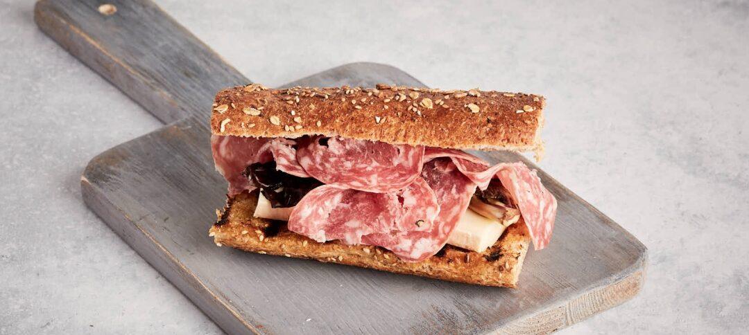 Belegtes Brötchen mit Taleggio-Käse, Perlweinsalami und geschmorter Radicchio
